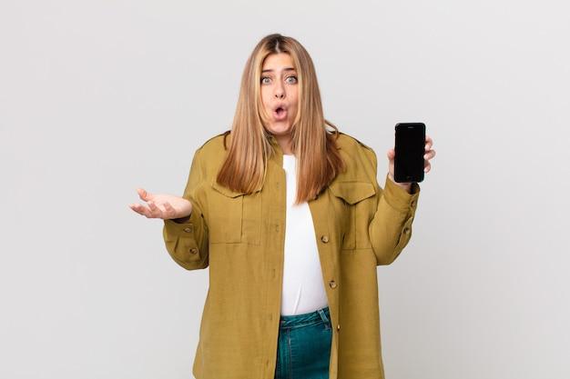 Curvy bella donna bionda stupita, scioccata e stupita con un'incredibile sorpresa e con in mano uno smartphone