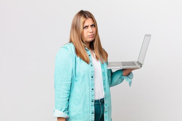 Bella donna formosa che tiene un laptop