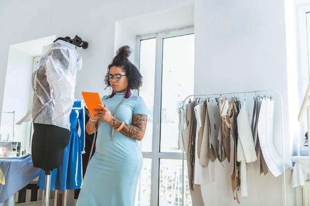 Forme sinuose. attenta donna dai capelli corti con panino sciatto che rimane nell'area di cucito e controlla le informazioni sul suo tablet