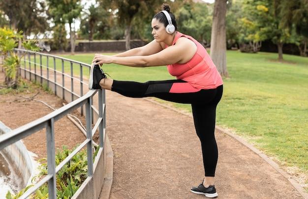 Donna formosa che fa routine di allenamento sportivo all'aperto nel parco cittadino