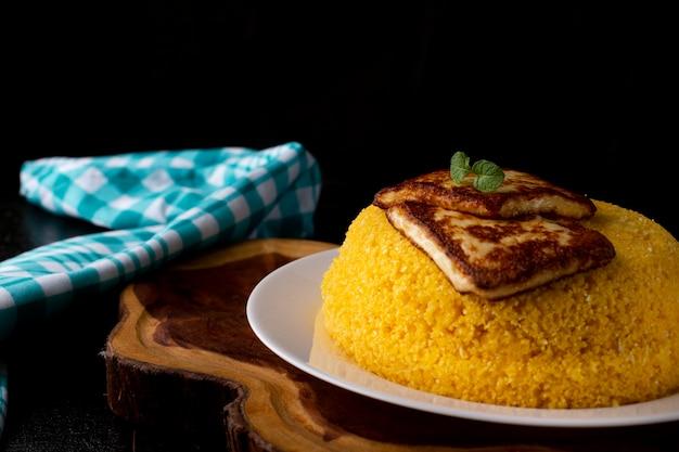 Cuscuz con formaggio, cibo tipico del nordest su un piatto bianco