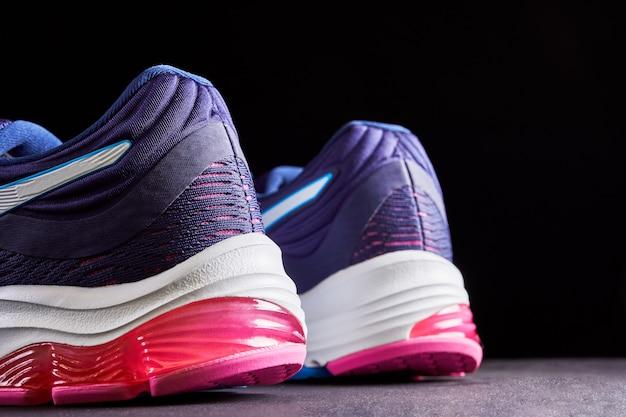 Scarpe da corsa imbottite. scarpe da ginnastica femminili per correre su sfondo scuro. moda scarpe sportive alla moda.