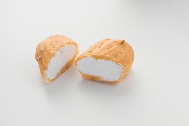 L'eclair della torta del taglio della crema si trova su una priorità bassa bianca.