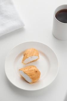 La torta eclair tagliata alla crema si trova su un piatto bianco con un bicchiere sullo sfondo.