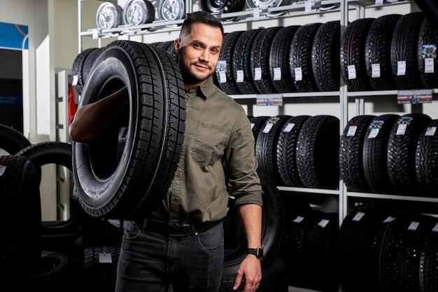 Cliente nella stazione di servizio del negozio di riparazione o manutenzione auto con pneumatici per ruote automobilistiche, indossando abiti casual. auto, auto, concetto di trasporto