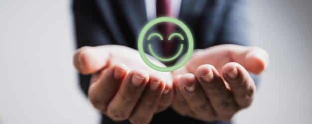Concetto di esperienza del cliente, mano ravvicinata dell'uomo d'affari che tiene una faccina sorridente felice per la migliore valutazione