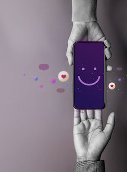 Concetto di esperienza del cliente. cliente felice che dà un'emoticon sorridente tramite telefono cellulare al marchio. feedback su smartphone. recensione positiva. sondaggio di soddisfazione online
