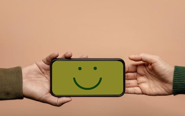 Concetto di esperienza del cliente. cliente felice che dà un'emoticon sorridente tramite telefono cellulare al marchio. feedback su smartphone. recensione positiva. sondaggio sulla soddisfazione