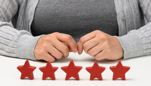 Concetto di feedback sull'esperienza del cliente. cinque stelle rosse, la migliore valutazione di servizi eccellenti con una mano femminile da incontrare. tavolo bianco