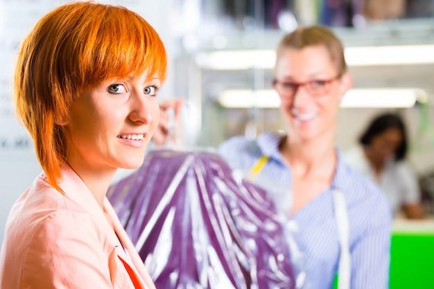 Cliente in lavanderia o lavaggio a secco di tessuti