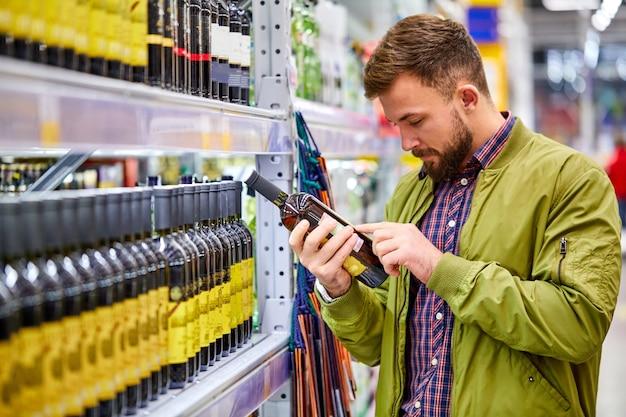 Il maschio del cliente che legge la composizione nel vino nel supermercato, desidera comprare l'alochol per le feste