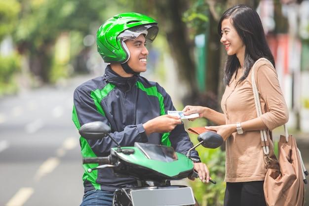 Il cliente paga per la sua corsa al tassista del motociclo