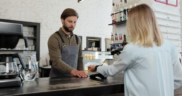 Cliente che paga con uno smartwatch contactless nfc con un distributore di carte. pagare in un bar con uno smartwatch. tecnologia.