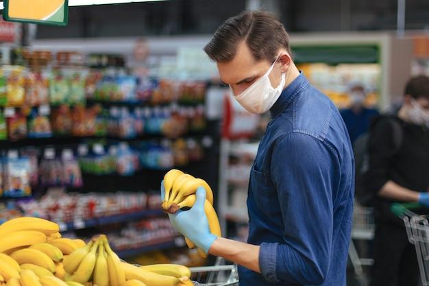Cliente in guanti protettivi che scelgono le banane in un supermercato. igiene e sanità