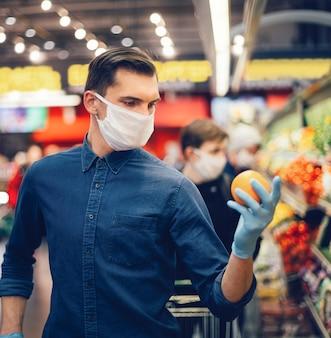 Cliente in guanti protettivi scegliendo frutta in un supermercato. igiene e assistenza sanitaria