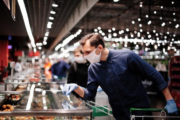 Cliente in guanti protettivi guardando i prodotti nel frigorifero.