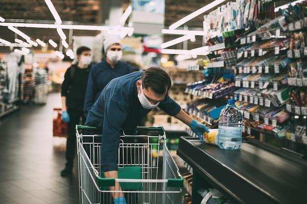 Il cliente mette i propri acquisti sul bancone del supermercato Foto Premium