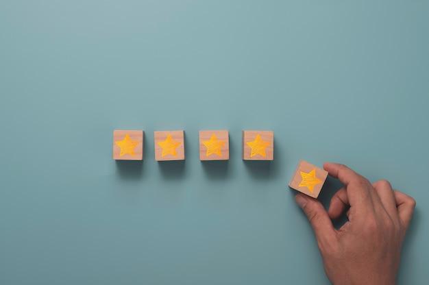 La soddisfazione del cliente e il concetto di valutazione del servizio del prodotto, mano che tiene e metti la stella gialla a cinque stelle con lo spazio della copia.