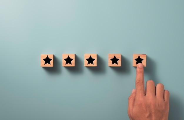La soddisfazione del cliente e il concetto di valutazione del servizio del prodotto, mano che tocca la stella a cinque stelle con lo spazio della copia.