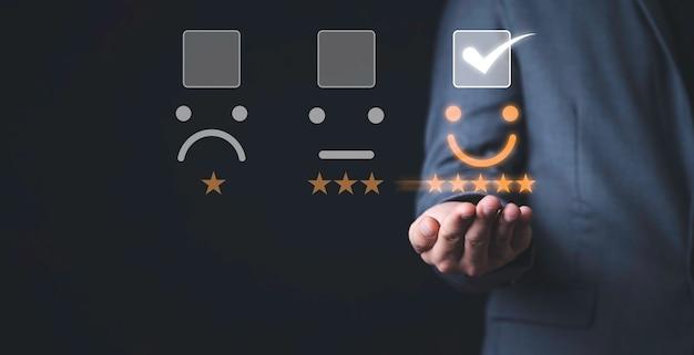 Concetto di sondaggio sulla soddisfazione del cliente, uomo d'affari toccando l'icona della faccina sorridente con cinque stelle gialle e il segno corretto per valutare il prodotto e il servizio.