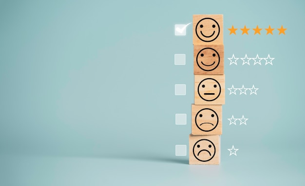 Concetto di sondaggio sulla soddisfazione del cliente, schermo di stampa delle icone del volto umano su un cubo di legno con stelle e segno per valutare il prodotto e il servizio.