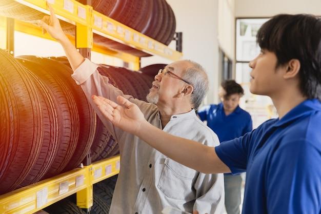 Il cliente che seleziona i pneumatici per auto in garage e il personale di vendita consiglia vari tipi di pneumatici per veicoli
