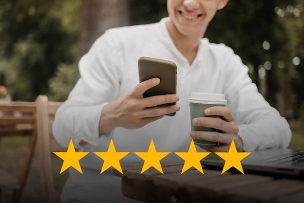 Concetto di servizio al cliente. l'uomo con un punteggio di 5 stelle sul suo telefono. sistema di classificazione online.