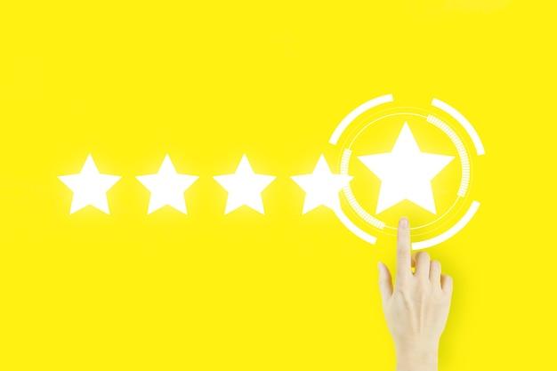 Concetto di valutazione del servizio clienti. il dito della mano della giovane donna che indica con l'ologramma cinque stelle su fondo giallo. concetto di esperienza del cliente. recensione, valutazione, soddisfazione.