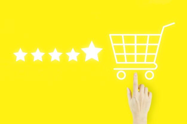 Concetto di valutazione del servizio clienti. il dito della mano della giovane donna che indica con l'ologramma carrello della spesa e cinque stelle 5 valutazione su fondo giallo. aumentare la valutazione del rating e il concetto di classificazione.