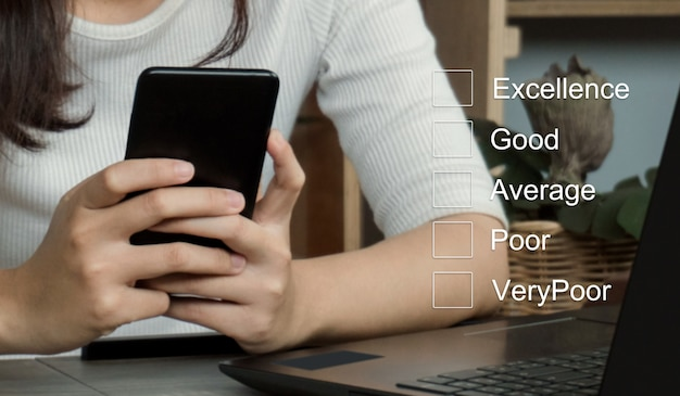 Concetto di valutazione del servizio clientidonne d'affari mano mettendo il segno di spunta su una casella di controllo sullo smartphone