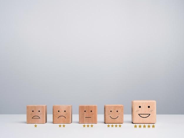 Valutazione del servizio clienti, feedback e concetto di indagine sulla soddisfazione. blocchi di cubo di legno con una simpatica emoticon con facce emotive e stelle dorate di valutazione su sfondo bianco con spazio di copia.