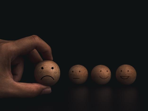 Valutazione del servizio clienti, valutazione, feedback e concetto di indagine sulla soddisfazione. mano che tiene la faccia triste e fallita dell'emoticon sulla palla di legno su sfondo scuro.