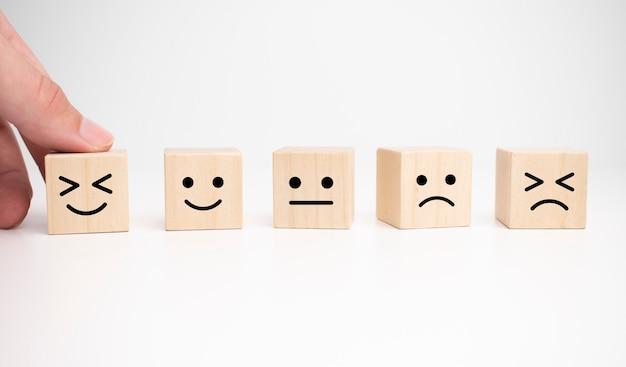 Concetti di valutazione del servizio clienti e indagine sulla soddisfazione. la mano del cliente ha scelto il simbolo della faccia sorridente del viso felice sul cubo di legno, spazio di copia
