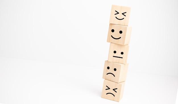 Concetti di valutazione del servizio clienti e indagine sulla soddisfazione. simbolo del viso sorridente del viso felice sul cubo di legno, spazio della copia