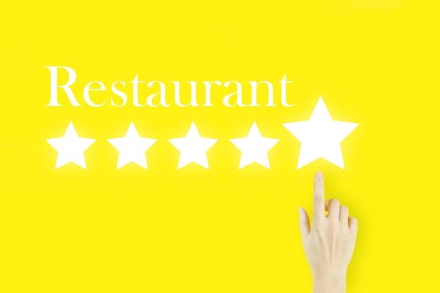 Concetti di valutazione del servizio clienti e indagine sulla soddisfazione. dito della mano della giovane donna che indica con l'ologramma cinque stelle e ristorante del testo su fondo giallo. recensione, valutazione, soddisfazione.