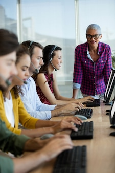 Istruttore esecutivo del servizio clienti che monitora il suo team in ufficio