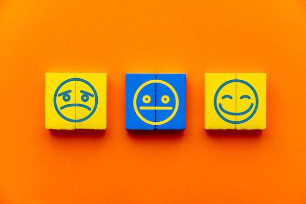 Esperienza del servizio clienti e concetto di indagine sulla soddisfazione con espressioni facciali negative, neutre e positive su cubo di legno sul tavolo, sfondo arancione