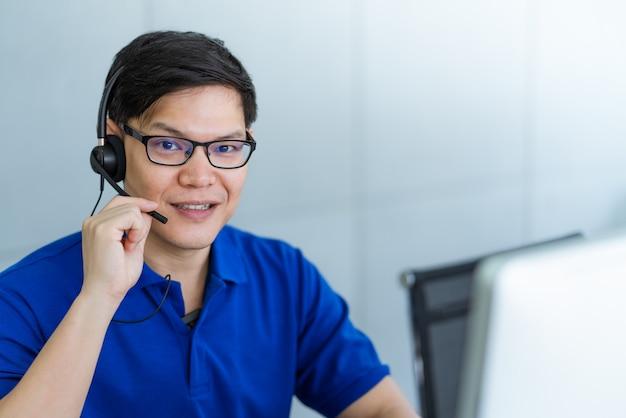 Cuffia d'uso dell'uomo di servizio di assistenza al cliente che parla con il cliente all'ufficio della call center