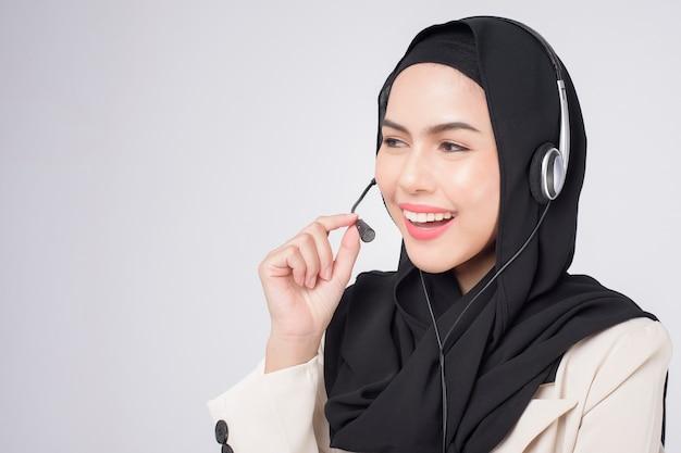 Operatore del servizio clienti donna musulmana in tuta che indossa la cuffia su sfondo bianco studio