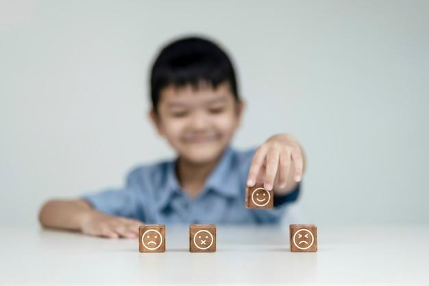 Servizio clienti e concetto di soddisfazione, i bambini mostrano un feedback con l'icona del sorriso felice del cubo di legno del viso sorridente per dare soddisfazione nel servizio. voto molto colpito.