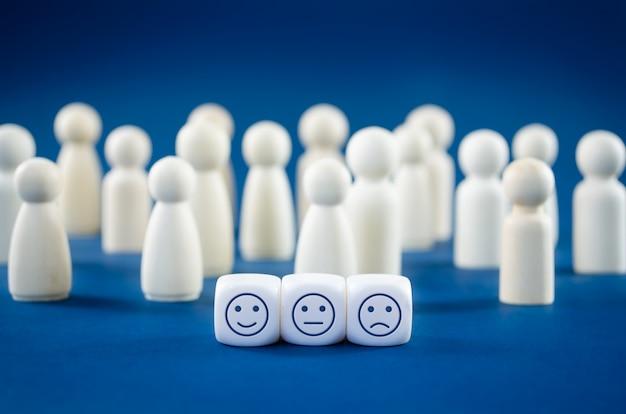 Concetto di soddisfazione del servizio clienti con tre blocchi bianchi con diverse espressioni di soddisfazione su di loro con figure di legno nello spazio
