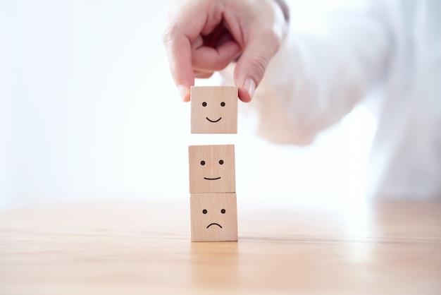 Cliente che mostra valutazione con l'icona felice sul cubo di legno