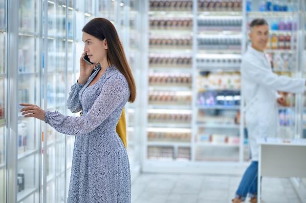Cliente che parla allo smartphone in presenza di un farmacista