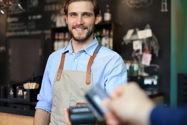 Cliente che utilizza carta di credito per il pagamento al proprietario presso il bar ristorante, tecnologia senza contanti.
