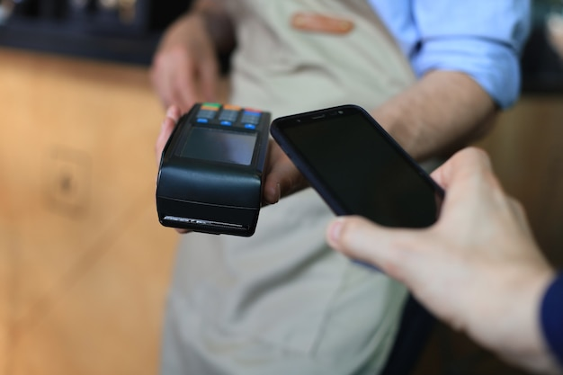 Cliente che utilizza lo smartphone per il pagamento al proprietario al ristorante caffetteria, tecnologia senza contanti.