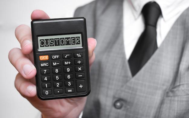 Iscrizione di testo parola cliente sulla calcolatrice in una mano maschio di un uomo d'affari in camicia bianca e cravatta blu