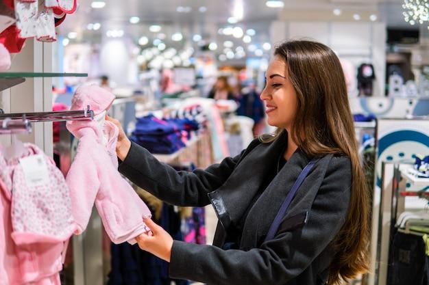Cliente giovane donna che sceglie vestiti per bambini o abbigliamento per bambini nel negozio. acquisto in negozio per neonati