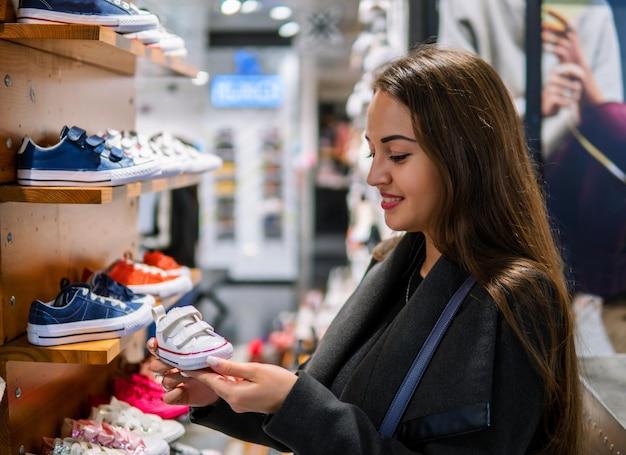 Cliente giovane donna che sceglie scarpe da ginnastica per bambini o abbigliamento per bambini nel negozio. acquisto in negozio per neonati
