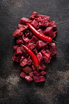 Tagliare la carne in piccoli pezzi con sale marino, erbe secche e peperoncino su fondo di ardesia o cemento scuro. vista dall'alto.