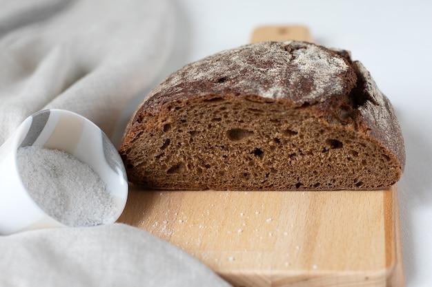 Tagliare il pane di segale nero con sale su una tavola di legno